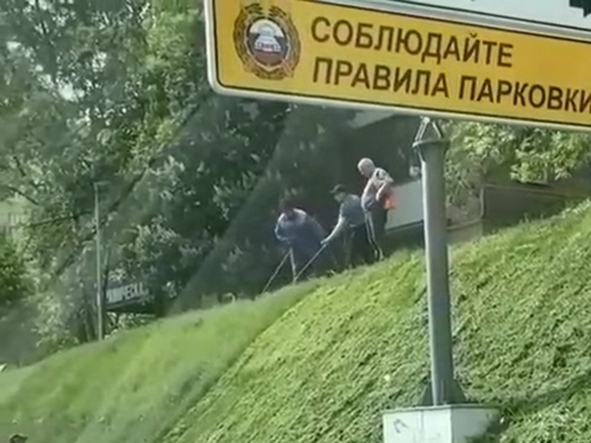 Рабочие в Москве косят газон