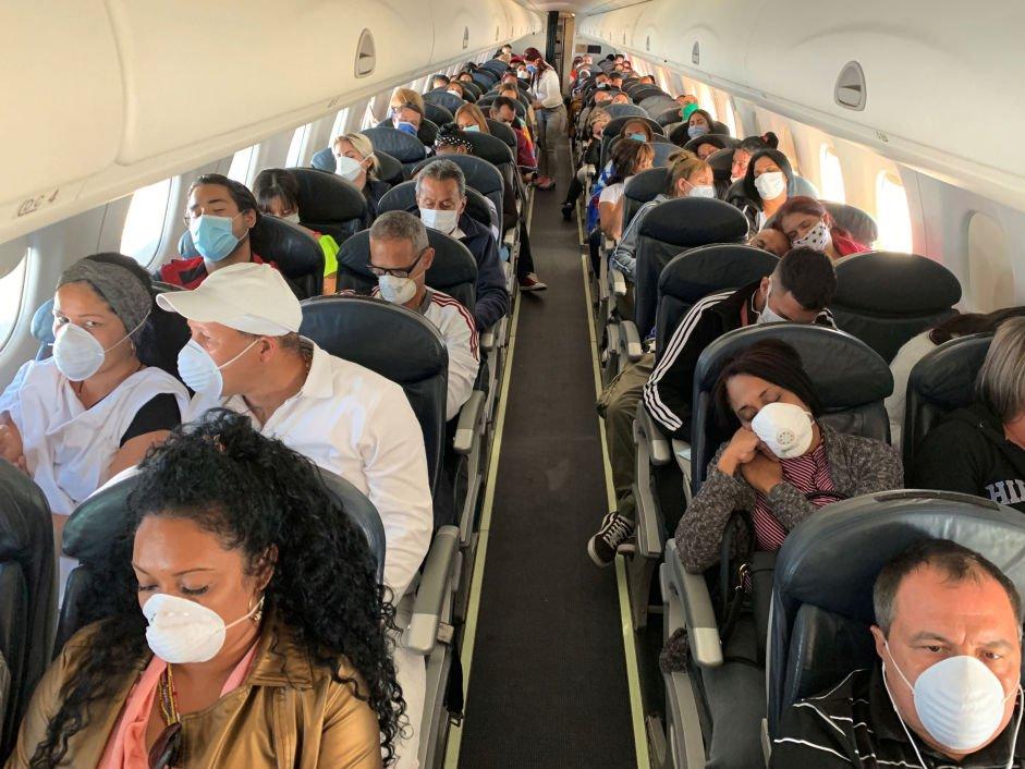 Пассажиры в самолете в масках