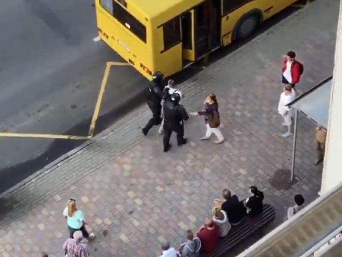 ОМОНовцы ведут мужчину в городской автобус в Мниске