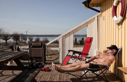 Заключенный, приговоренный к 16 годам за убийство, принимает солнечные ванны на крыльце своего коттеджа.