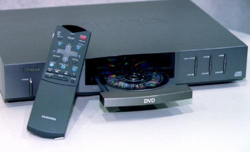 """Новый DVD-видеоплеер, изготовленный фирмой """"Toshiba"""" и представленный на выставке потребительской электроники  в Лас-Вегасе 5 января 1996 г. Плеер считывает информацию с пятидюймового оптического диска, вмещающего до 133 минут цифрового видео и звука."""