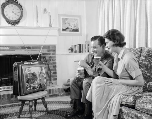 Примерно 1960: молодая пара смотрит портативный телевизор в гостиной.