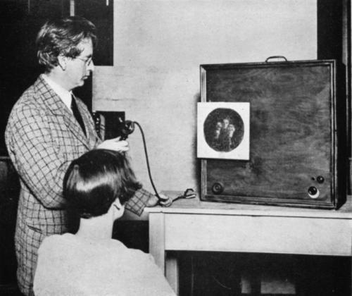 Бэрд начал экспериментировать с системами визуализации в начале 1920-х. В 1924 году он сумел передать по проводам первое контурное изображение, а к 1925 году уже был в состоянии передавать узнаваемые человеческие лица. В 1926 году он открыл первый в мире телецентр, названный им 2TV.На фото: Джон Лоуги Бэрд перед экраном одного из первых телепередатчиков («прибор беспроводного видения»).