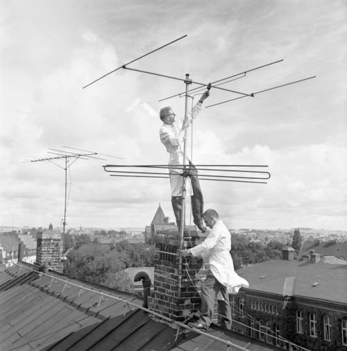 Заря телевидения в Швеции, 1953 г. Двое мужчин в белых халатах монтируют антенну.
