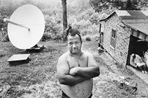 Берт Джетт  гордо стоит во дворе своего дома неподалёку от городка Блу Крик, Элквью, Западная Вирджиния, где он и его два брата установили спутниковую тарелку стоимостью 7800 долларов, чтобы улучшить прием ТВ сигнала (снимок сделан 14 июля 1981 г.).