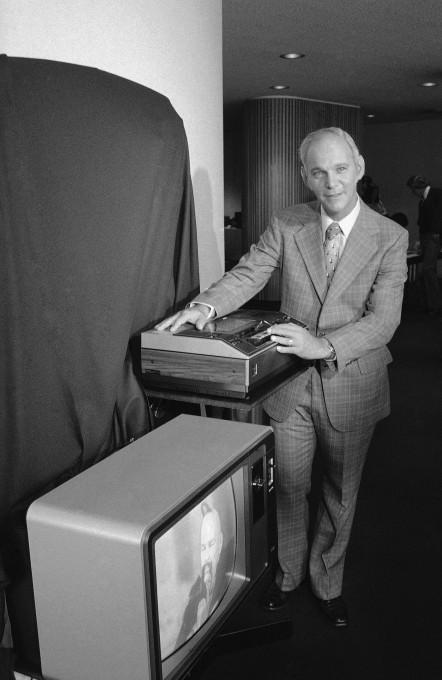 Рой  Поллак  вице-президент и генеральный менеджер корпорации потребительской электроники RCA, демонстрирует новый видеомагнитофон в Нью-Йорке 23 августа 1977 г. Устройство предназначалось для использования в домашних условиях, стоило 1000 долларов в розничной продаже и могло непрерывно проигрывать кассеты с телевизионными программами в течение четырех часов.