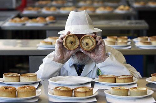 Судья «World Pie Championship» Джон Янг (John Young) позирует с двумя шотландскими пирогами на чемпионате в Данфермлине, Шотландия.