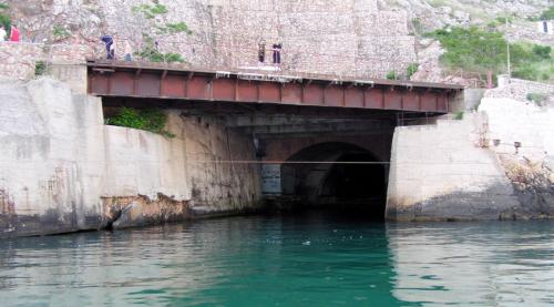 База подводных лодок Во времена СССР это место обозначалось на секретных картах только как «объект 825 ГТС». Именно здесь, неподалеку от Балаклавы, располагалась база подводных лодок. Объект был построен еще в 1961 году, в рамках программы по усилению противоатомной защиты страны. Попасть внутрь можно было только через штольню или с северной части горы Таврос, причем обе двери имели тщательную маскировку и были водонепроницаемыми. Территория базы занимала целых 5100 квадратных метров: собственный госпиталь, своя пекарня и даже свой спортивный центр. В случае нападения на страну потенциального противника на базе с легкостью разместилось бы все население Балаклавы, а припасов хватило бы на целых три года.
