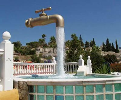 Труба и опора фонтана под названием «Волшебный Кран», который является достопримечательностью города Кадиз, Испания, спрятана в струе воды.