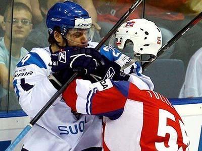 «Невидимый хоккеист». Фотограф умудрился запечатлеть, как в пылу борьбы с норвежского игрока слетела каска.