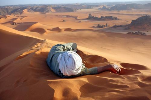 Заслуженный отдых в СахареНа этой фотографии гид Мусса Мачер, который был снят на вершине высочайшей дюны в Сахаре. Мусса отдыхал, ожидая нас, пока мы совершали 45-минутный подъем на вершину. Спуск перекатами и прыжками занял всего 10 минут.