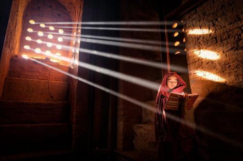 Источник светаМолодой монах нашел идеальный источник света, чтобы читать книгу внутри своей пагоды.