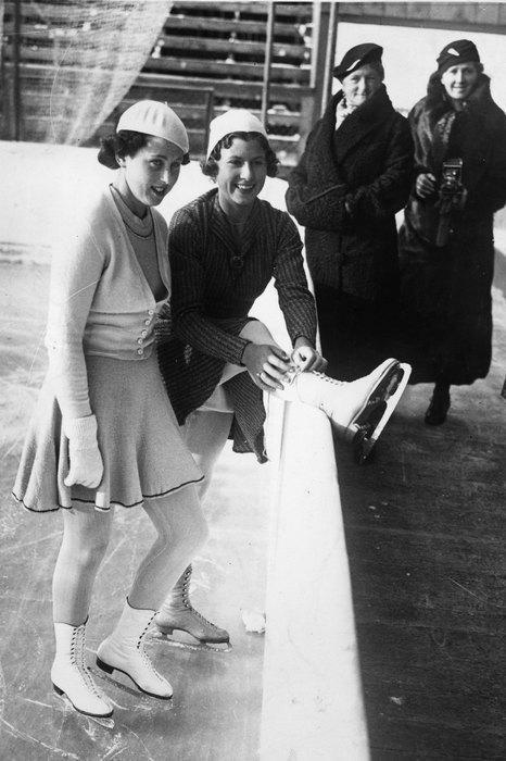 1936  В 1936 году костюмы фигуристов уже менее закрытые и более удобные — юбки становятся заметно короче, но перчатки и головные уборы по‑прежнему остаются в экипировке.